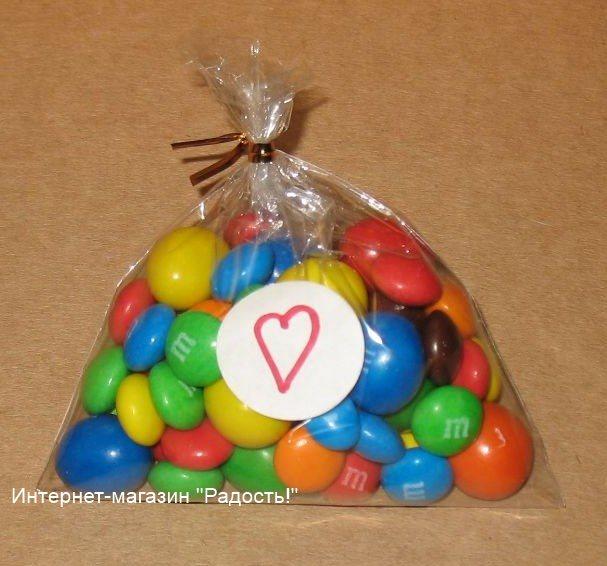 целлофановый пакет с конфетами: верх пакетика перевязан проволочным твистом золотого цвета