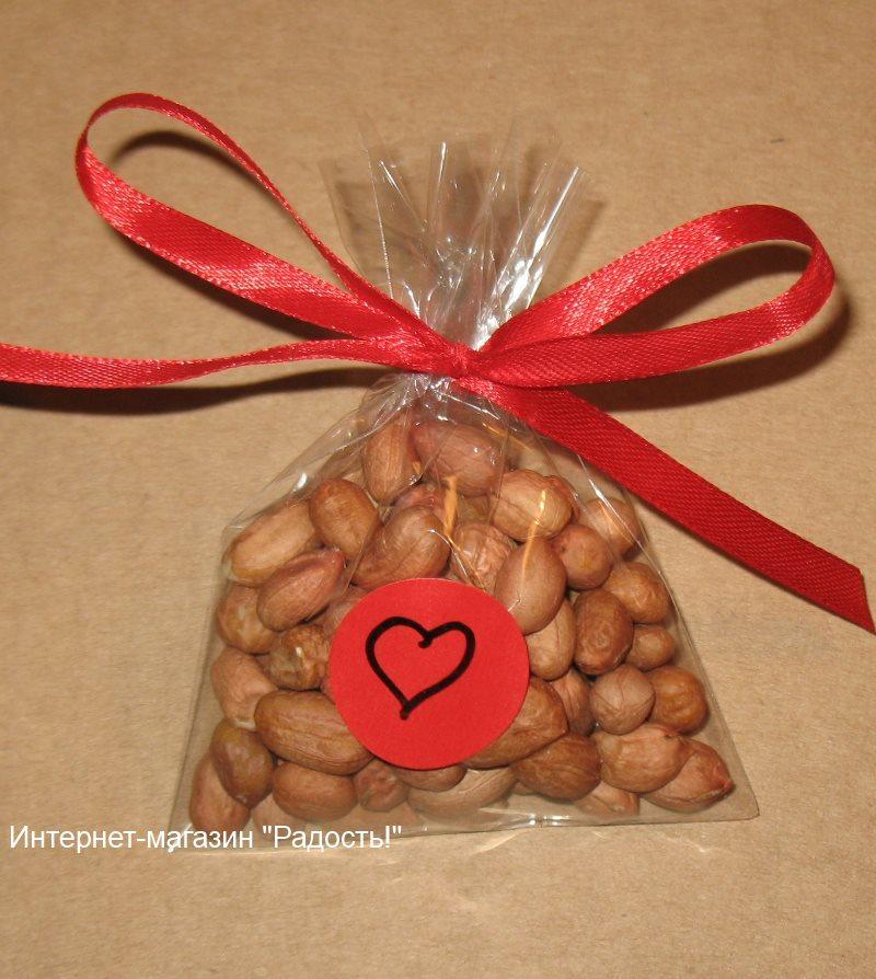 орехи арахис упакованы в прозрачный пакет из целлофана и завязаны атласной ленточкой красного цвета, фото