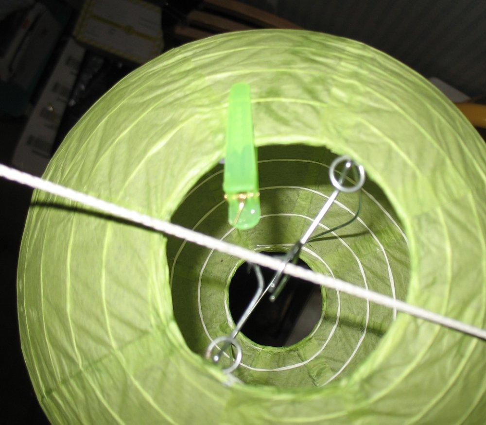 """Способ 2 - для тех случаев, когда присутствует ветер (сквозняк), раскачивающий фонарики: подсветка снизу или уверху закрепляется на фонарике пластиковым """"крокодилом"""" (заколка для волос)"""