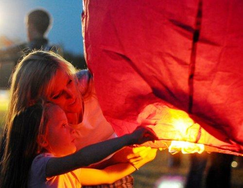 Девочка с мамой запускают небесный летающий фонарик