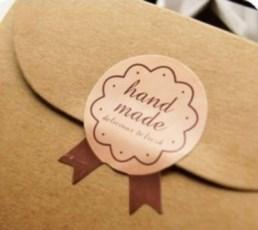 "Бежевый стикер ""Handmade"" в виде бантика запечатывает картонную крафт-коробку"